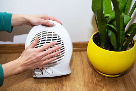 The girl holds her hands near the plastic fan heater and warms her hands, adjusting the temperature at home, the flow of heat