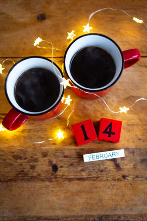 Two cups of coffee in red cups on a background of garlands. Postcard with date and month. Morning breakfast for Valentine's Day. Love concept