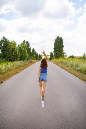 Attractive girl, stands posing, hands up in the middle of an asphalt road near the field, copies space for content.