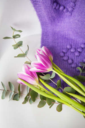 Beautiful purple tulip with eucalyptus on a white chair along with a purple sweater. Spring mood, March 8th