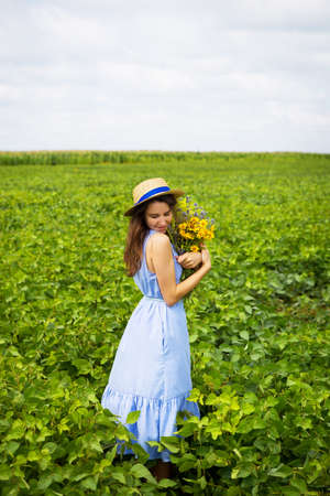 the girl is standing in the field with a bouquet of yellow flowers and a straw hat. Stock Photo