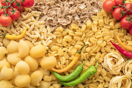 A lot of different raw pasta and vegetables for background Archivio Fotografico