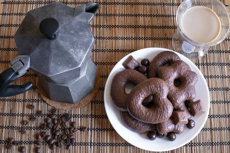 Gingerbread cookies in chocolate with hot coffee on placemat Archivio Fotografico