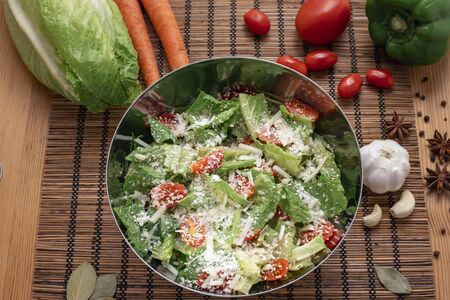 Lettuce and cherry salad in an iron bowl on placemate Archivio Fotografico