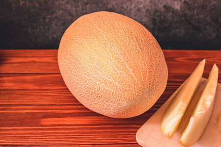Melon on wooden table with black background