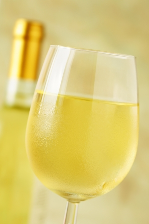 Close-up of a ice cold glass of white wine covered with water drops - condensation photo