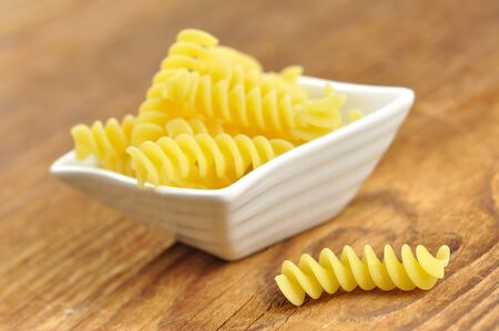 Uncooked fusilli in a small bowl, italian pasta, wooden background, selective focus photo
