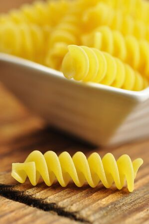 Uncooked fusilli in a small bowl, italian pasta, wooden background, selective focus Stock Photo - 15291270