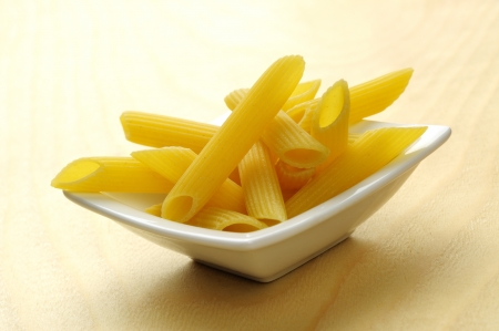 Small bowl of italian penne pasta, wooden background photo