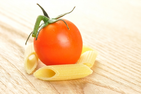 Several uncooked penne pasta and a cherry tomato on a wooden chopping board, closeup Stock Photo - 15629779