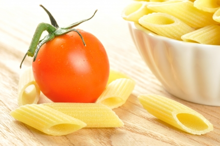 Several uncooked penne pasta and a cherry tomato on a wooden chopping board, closeup Stock Photo - 15629778