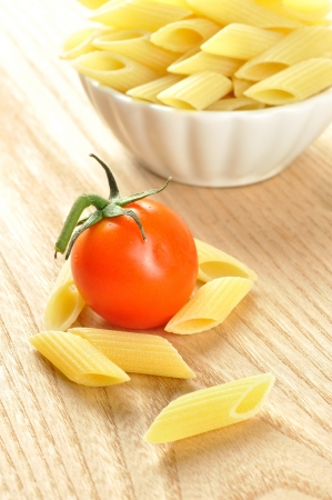 Several uncooked penne pasta and a cherry tomato on a wooden chopping board, closeup photo