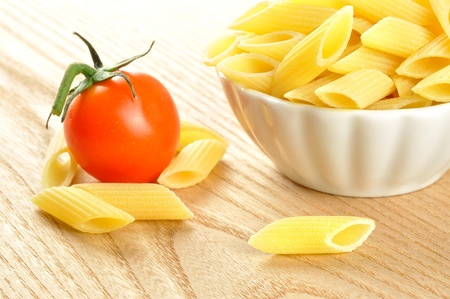 Several uncooked penne pasta and a cherry tomato on a wooden chopping board, closeup Stock Photo - 15629784