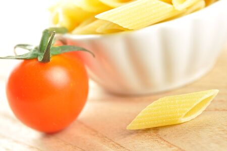 Several uncooked penne pasta and a cherry tomato on a wooden chopping board, closeup Stock Photo - 15629772