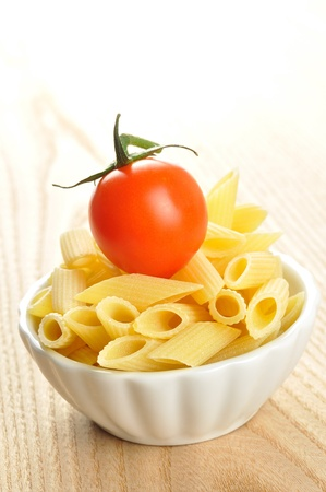Several uncooked penne pasta and a cherry tomato in a small bowl photo