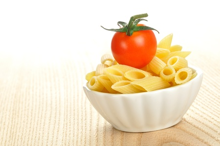 Several uncooked penne pasta and a cherry tomato in a small bowl Stock Photo - 15629773