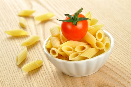 Several uncooked penne pasta and a cherry tomato in a small bowl Stock Photo - 15629782