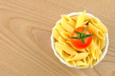 Several uncooked penne pasta and a cherry tomato in a small bowl Stock Photo - 15629786