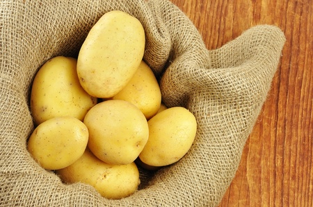 Raw potatoes in jute sack on a old wooden chopping board photo