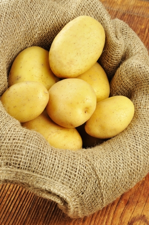 Raw potatoes in jute sack on a old wooden chopping board