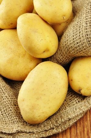 papas: Las patatas crudas en saco de yute en una tabla de cortar de madera vieja