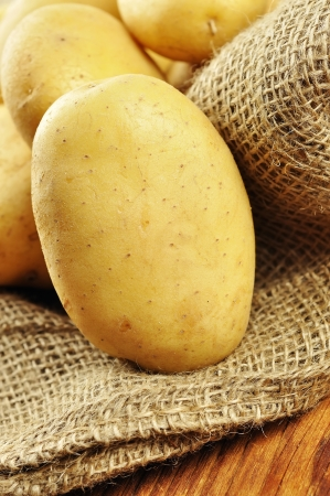 earthy: Raw potatoes in jute sack on a old wooden chopping board