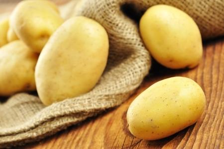 Syrové brambory v juty pytel na starém dřevěném prkénku Reklamní fotografie