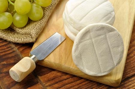 Italská tomino sýr na dřevěném prkénku, italské předkrm