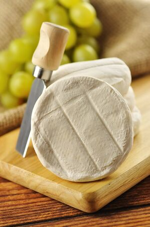 Italian tomino cheese on a wooden chopping board, italian appetizer photo