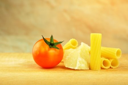 Raw tortiglioni pasta with parmesan and cherry tomato, selective focus photo