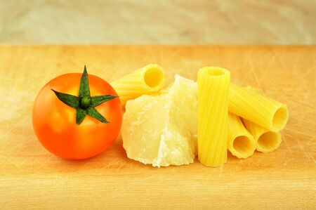 Raw tortiglioni pasta with parmesan and cherry tomato photo