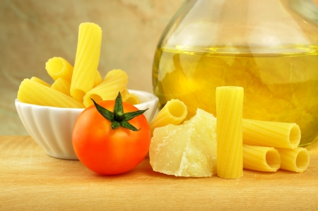 Raw tortiglioni pasta with parmesan, cherry tomato and olive oil photo