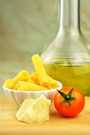 Raw tortiglioni pasta with parmesan, cherry tomato and olive oil, selective focus photo