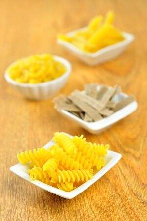 Several small bowls of different types of raw pasta on a wooden chopping board, selective focus Stock Photo