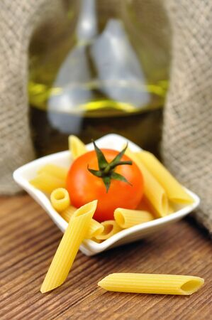 Raw penne pasta in a small bowl, selective focus Stock Photo - 16391253