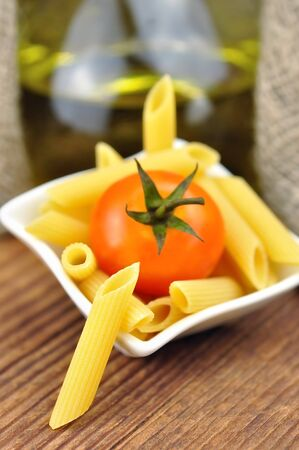 Raw penne pasta in a small bowl, selective focus photo