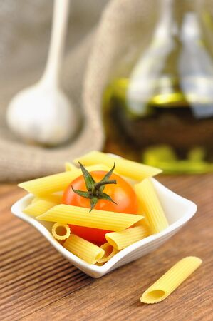 Raw penne pasta in a small bowl, selective focus Stock Photo - 16391268