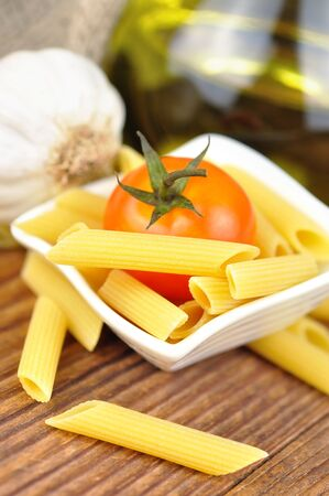 Raw penne pasta in a small bowl, selective focus Stock Photo - 16391267