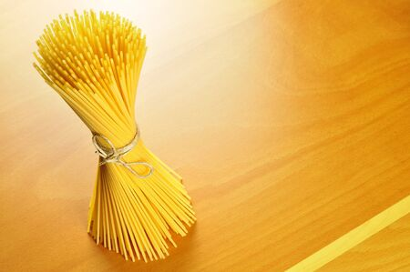 Spaghetti pasta on a wooden chopping board, selective focus Stock Photo - 16462502
