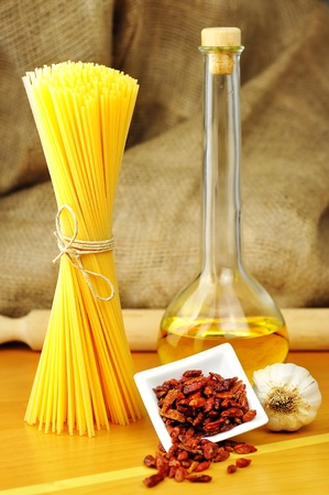 Raw ingredients for spaghetti aglio, olio e peperoncino  garlic, oil, and chili , selective focus photo