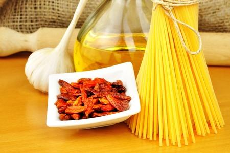 Raw ingredients for spaghetti aglio, olio e peperoncino  garlic, oil, and chili , selective focus