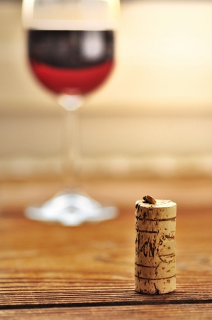Cork and glass of italian red wine on a table in oak, closeup, selective focus photo