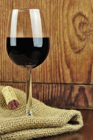 Glass and cork of fine italian red wine, wooden background photo