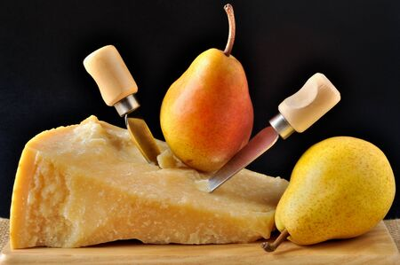 Parmesan and pears on a wooden chopping board photo