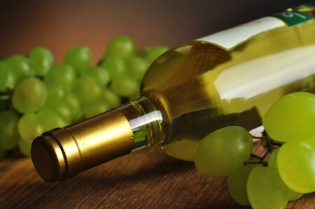 Bottle of fine italian white wine with grapes photo