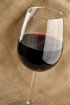 Glass of fine italian red wine, jute background photo