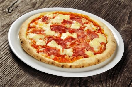 Pizza se šunkou a mozzarellou na starý dřevěný stůl