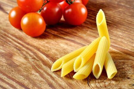 Uncooked penne pasta and cherry tomatoes on a old wooden table photo