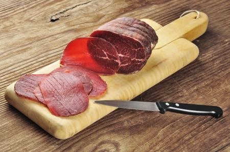 salami: Bresaola en rodajas sobre una tabla para cortar; Foto de archivo