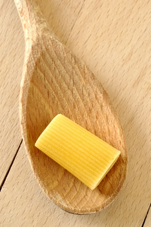 Uncooked rigatoni pasta on a wooden spoon photo